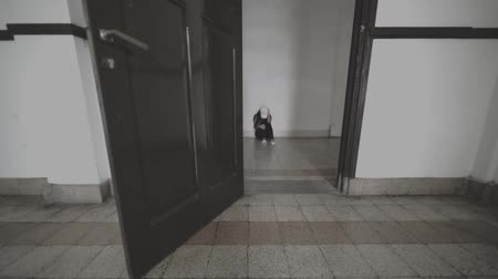 банда : Depressed young woman crying on the corridor while sitting on the floor inside a building