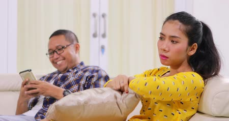 addicted : Mobile phone addiction concept. Angry woman grabbing her boyfriend cellphone after ignored by him on the sofa at home. Shot in 4k resolution Stock Footage