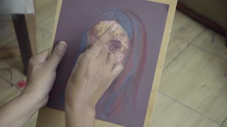 face painting : JAKARTA - Indonesia. April 20, 2018: Male painter make a woman painting on the canvas using pastel crayon in the studio Stock Footage