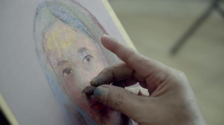 şaheser : JAKARTA - Indonesia. April 20, 2018: Male painter hand painting a woman face using pastel crayon on the canvas in the studio Stok Video