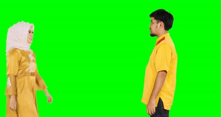 perdão : Eid Mubarak concept. Muslim man kiss his wife while handshaking and forgiving to each other during Eid Mubarak in front of green screen background. Shot in 4k resolution Vídeos