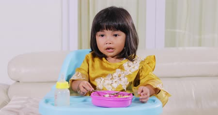 frasco pequeno : Cute little muslim girl having lunch while sitting on highchair in dining room at home. Shot in 4k resolution
