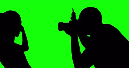professional photography : Silhouette of unknown man photographing a female model in the studio, shot in 4k resolution with green screen background