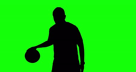 unknown : Silhouette of unknown basketball player dribbling a ball and standing in the studio. Shot in 4k resolution with green screen background