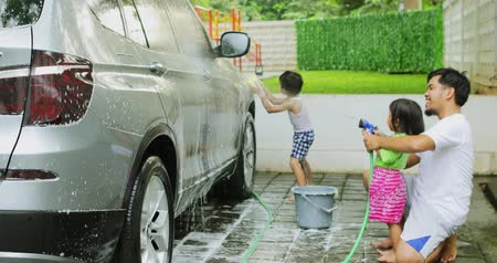сестры : Two cheerful kids and their father washing a car using a water hose and sponge at home. Shot in 4k resolution Стоковые видеозаписи