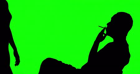 önlemek : Silhouette of man prohibited to smoke by a woman in the studio. Shot in 4k resolution with green screen background Stok Video