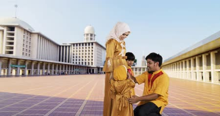 véu : Two muslim children and their mother kissing father hand in the Istiqlal Mosque at Jakarta, Indonesia. Shot in 4k resolution