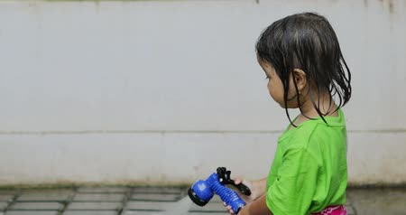 indonesian : Cute little girl playing a water hose alone outside at home. Shot in 4k resolution