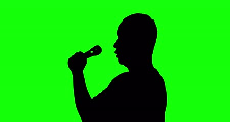 unidentified : Silhouette of a male classical singer singing with a microphone in the studio, shot in 4k resolution with green screen background
