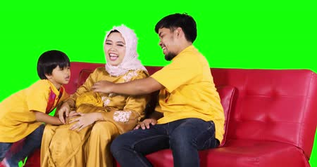 malajské : Cheerful muslim family relaxing together on the sofa while wearing islamic clothes in the studio, shot in 4k resolution with green screen background Dostupné videozáznamy