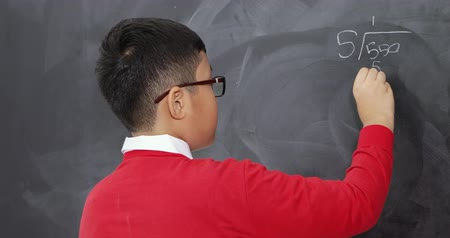 çözmek : Little boy holding a book and solve a math on blackboard while wearing glasses and smiling at the camera. Shot in 4k resolution Stok Video