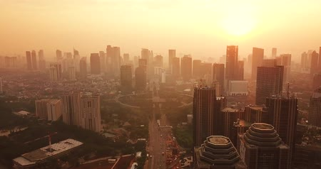 sudirman : JAKARTA, Indonesia - May 22, 2018: Beautiful aerial scenery of Sudirman CBD with skyscrapers and Semanggi flyover on foggy day at sunset time. Shot in 4k resolution