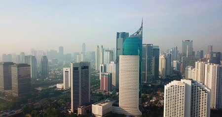 centrální čtvrť : JAKARTA, Indonesia - May 23, 2018: Aerial panorama of Jakarta city on foggy day with skyscrapers background from a drone flying backwards. Shot in 4k resolution