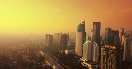 верный : JAKARTA, Indonesia - May 23, 2018: Bird eye view of dusk time with orange sky and skyscrapers background in Jakarta city. Shot in 4k resolution from a drone