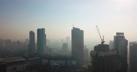 central business district : JAKARTA, Indonesia - May 23, 2018: Aerial landscape of misty morning in Jakarta downtown with skyscrapers view. Shot in 4k resolution from a drone flying forwards