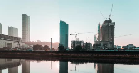 construction crane : JAKARTA, Indonesia - May 23, 2018: Time lapse footage of sunrise in Jakarta city with skyscrapers construction view on the riverside. Shot in 4k resolution Stock Footage
