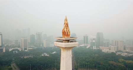 obelisco : JAKARTA, Indonesia - May 30, 2018: Aerial view of the Flame of Independence with gold-coated on National Monument Jakarta. Shot in 4k resolution from a drone