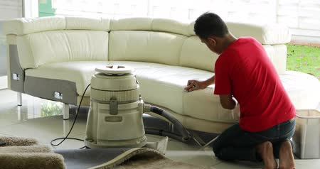 vácuo : JAKARTA, Indonesia - May 30, 2018: Male worker cleaning a sofa with vacuum cleaner at home. Shot in 4k resolution