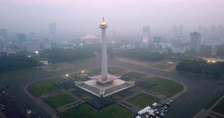 obelisk : JAKARTA, Indonesia - May 30, 2018: Bird eye view of National Monument Jakarta with fog at dusk time. Shot in 4k resolution from a drone