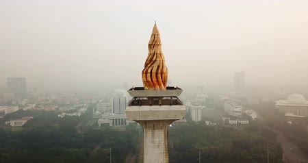 obelisco : JAKARTA, Indonesia - May 30, 2018: Aerial landscape of the golden peak of National Monument Jakarta on misty morning. Shot in 4k resolution