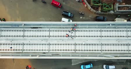 митрополит : JAKARTA, Indonesia - May 25, 2018: Top view of group of workers working on railroads construction for Jakarta Light Rail Transit. Shot in 4k resolution from a drone