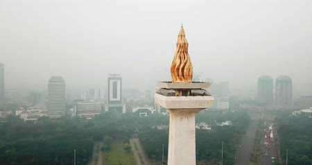 obelisco : JAKARTA, Indonesia - May 30, 2018: Aerial shot of National Monument with gold-coated Flame of Independence on misty morning in Jakarta city. Shot in 4k resolution