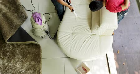 biscate : JAKARTA, Indonesia - May 30, 2018: Two male workers cleaning a sofa with a vacuum cleaner at home. Shot in 4k resolution Stock Footage