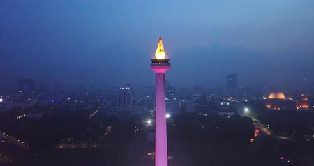 obelisk : JAKARTA, Indonesia - June 08, 2018: Exotic aerial view of Jakarta National Monument with colorful lights at night. Shot in 4k resolution