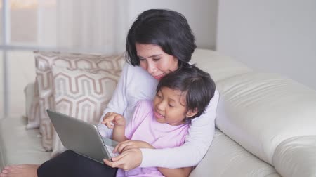 indonesian : Happy little girl and her mother sitting on the couch while using a laptop computer in the living room at home Stock Footage