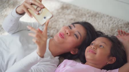 alma : Happy young mother and her daughter taking selfie photo together with a mobile phone while lying on the carpet at home. Shot in 4k resolution Stok Video