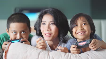 сестры : JAKARTA, Indonesia - June 05, 2018: Happy young mother cheering her kids while playing video game in the bedroom. Shot in 4k resolution