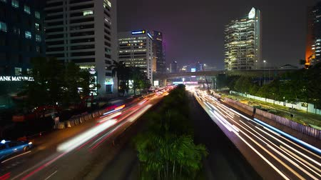 central business district : JAKARTA, Indonesia - June 22, 2018: Time lapse footage of blurred lights car on traffic jam at night in Jakarta city road. Shot in 4k resolution