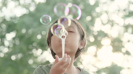 bańki mydlane : Happy Asian little girl blowing soap bubbles and smiling at the camera with blur background. Shot outdoors during summer time
