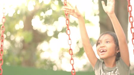 raised : Asian little girl playing on the swing at the park in summer time. Shot in 4k resolution