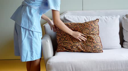 housekeeper : Cleaning service tidying up sofa in a five stars hotel rool