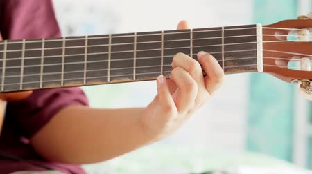 senza volto : Closeup of preteen hand learn to play a guitar in the bedroom at home. Shot in 4k resolution