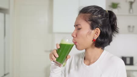hate : Young woman drinking a glass of vegetables juice with dislike expression in the kitchen at home. Shot in 4k resolution