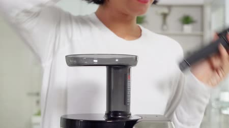 senza volto : Closeup of woman making vegetables juice with juicer machine in the kitchen at home. Shot in 4k resolution