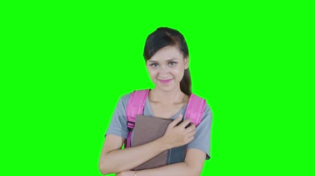 vysoká klíč : Slow motion of beautiful female high school student smiling at the camera while holding a book in the studio with green screen background