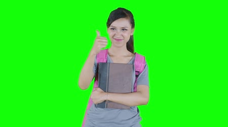 taça : Beautiful female high school student showing thumb up while holding book in the studio. Shot in 4k resolution with green screen background