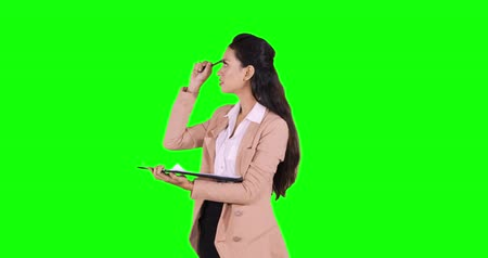 задумчивый : Young Asian businesswoman standing in the studio while writing on the clipboard and thinking idea. Shot in 4k resolution with green screen background Стоковые видеозаписи