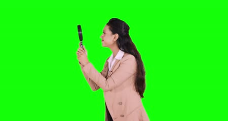 curioso : Young business woman looking through magnifying glass in the studio. Shot in 4k resolution with green screen background