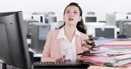 polinésia : Overworked business woman looks sleepy while working with computer and documents in the office. Shot in 4k resolution Stock Footage