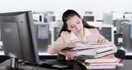 indonésio : Frustrated business woman searching document on a stack of documents in the office. Shot in 4k resolution