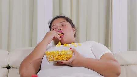insalubre : Overweight young woman eating a bowl of popcorn while sitting on the sofa and looks sleepy at home. Shot in 4k resolution