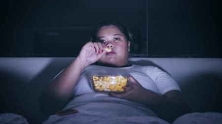 obżarstwo : Overweight woman enjoying a bowl of popcorn at night on the bed before sleep. Shot in 4k resolution
