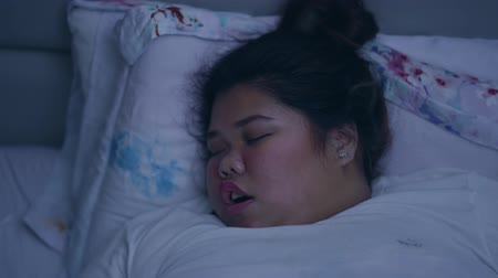 indonésio : Overweight young woman sleeping and snoring in her bed at night. Shot in 4k resolution