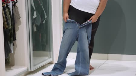 calças justas : Overweight woman trying to wear a jeans at home. Shot in 4k resolution