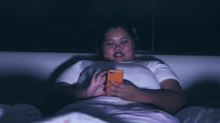bezsennosć : Overweight young woman using mobile phone on the bed at night. Shot in 4k resolution