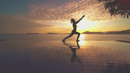 meditando : Silhouette of young girl practicing yoga on the pool at beach with sunrise background. Shot in 4k resolution